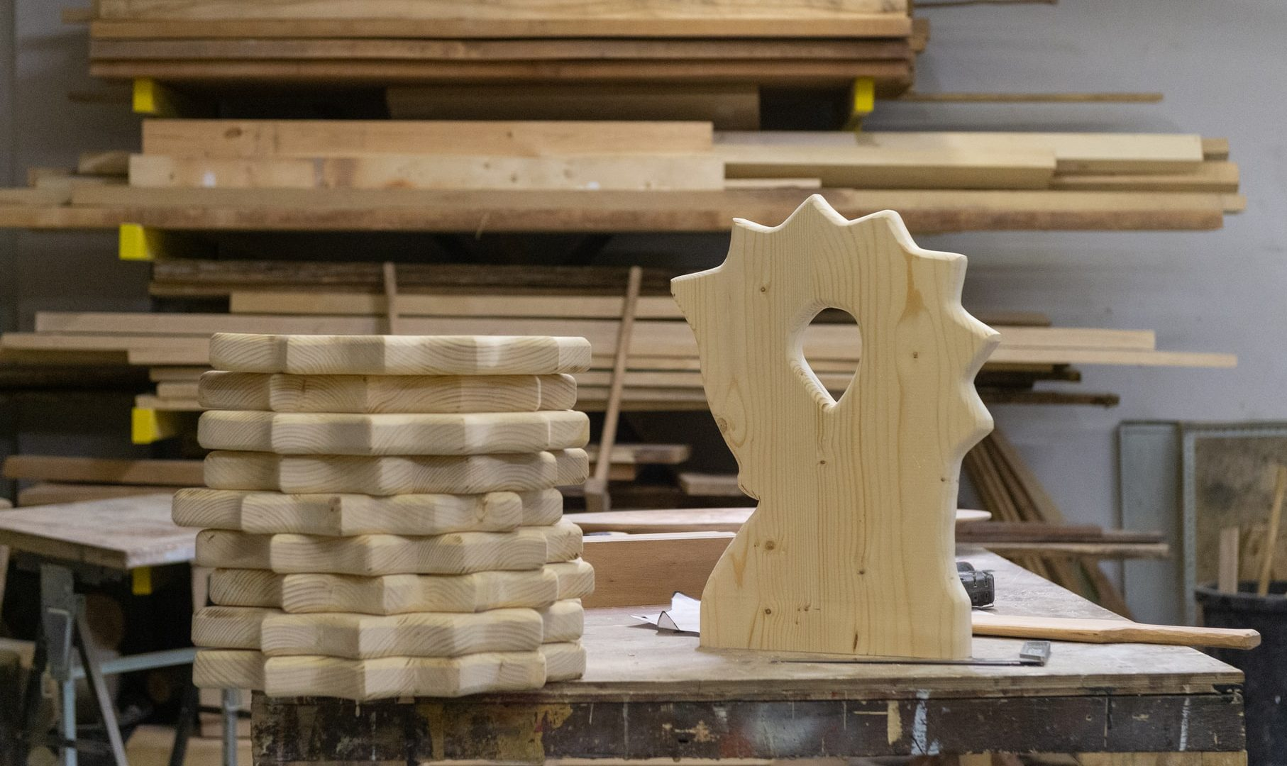 Sustainable design step 4, pile of carved wooden slabs next to an upright wooden slab